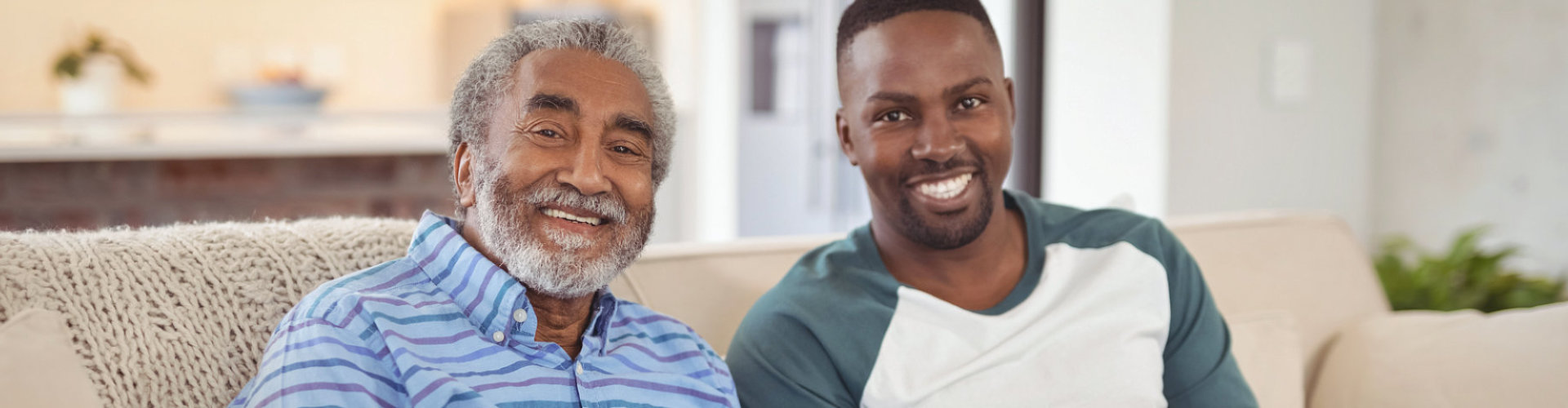 male caregiver and senior man are smiling